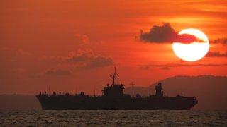 Navy vessel at sea at sunset