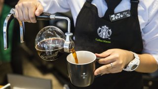 An employee pours coffee from a round glass jug into a mug at a Starbucks