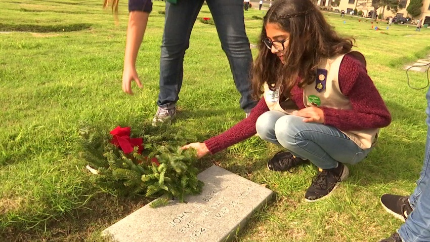 Girl is seen placing a wreath on Veterans tombstone