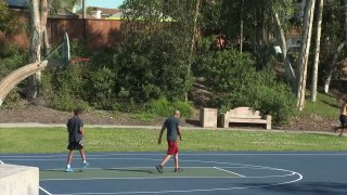 People playing basketball at a park in Chula Vista even though it's not allowed.