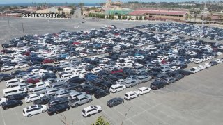 Hundreds of cars are parked close together in a large parking lot