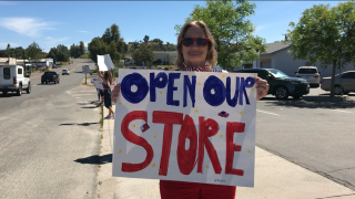 """Woman holds """"open our store' sign at rally in Ramona"""