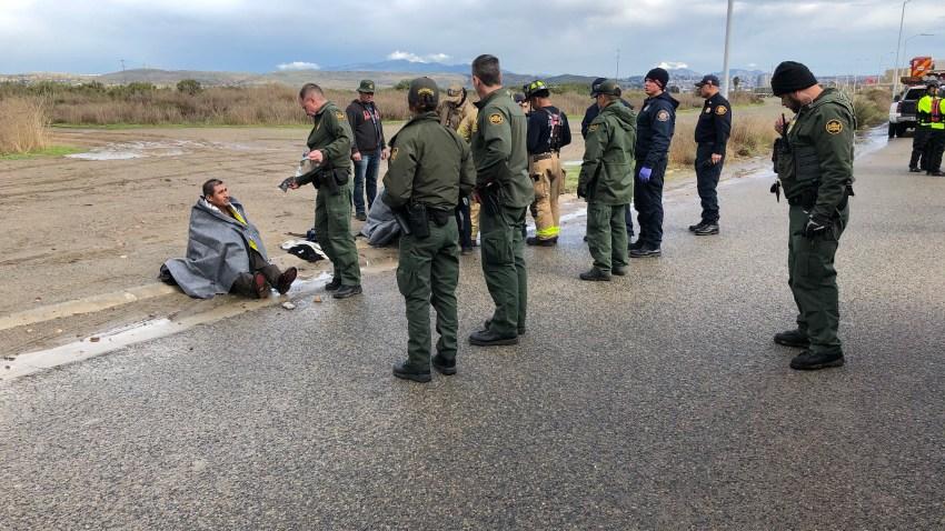 agentes del patrulla fronteriza frente a inmigrante sentado en el suelo con una cobija