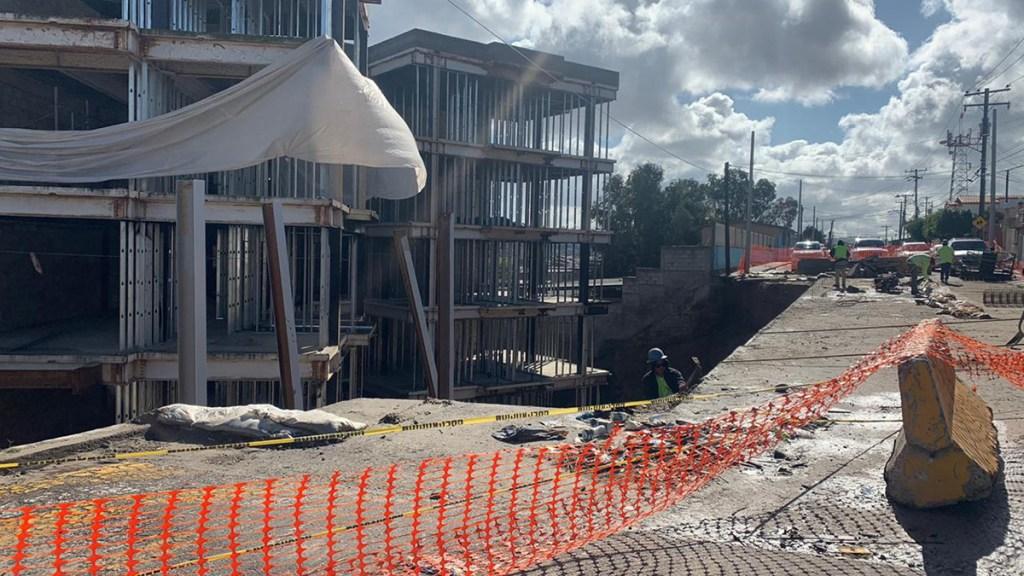 Un edificio en construcción se ve del lado izquierdo, a un lado de un derrumbe donde trabajadores estaban trabajando.