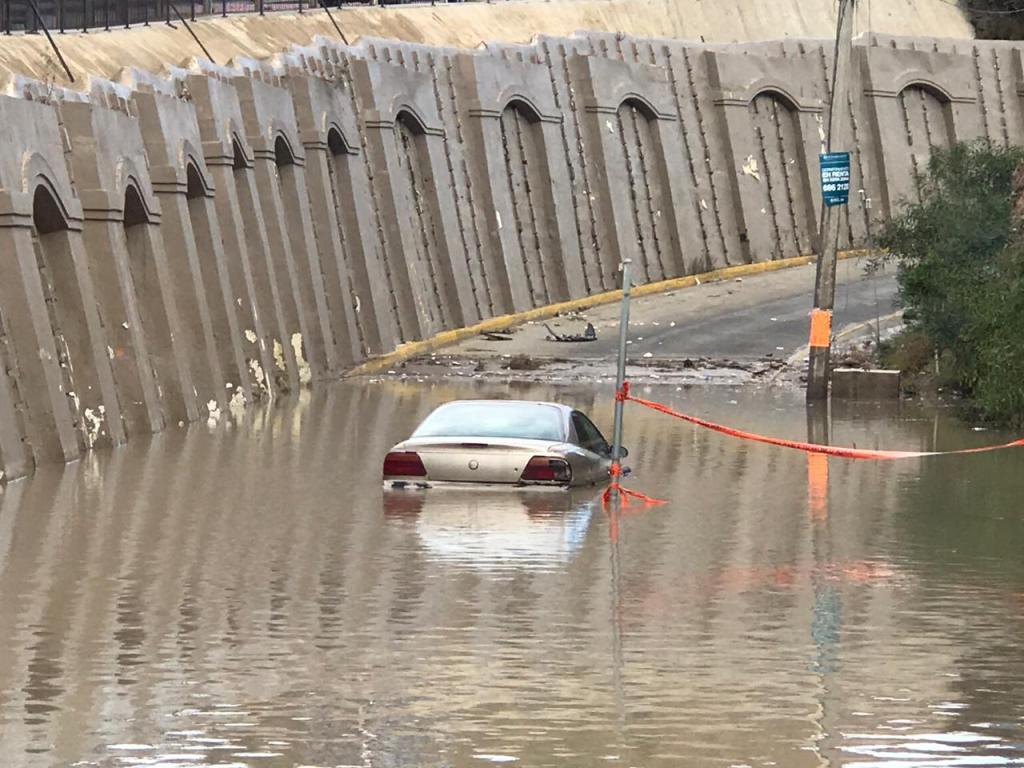 Un auto acaba sumergido en una calle en  la colonia Colinas de California en Tijuana.