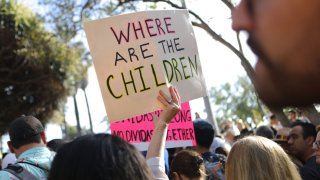 A protester holds a sign at the 'Families Belong Together March' against the separation of children of immigrants from their families