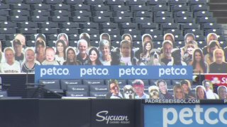 Cardboard cut-outs of people sit behind home plate at Petco Park