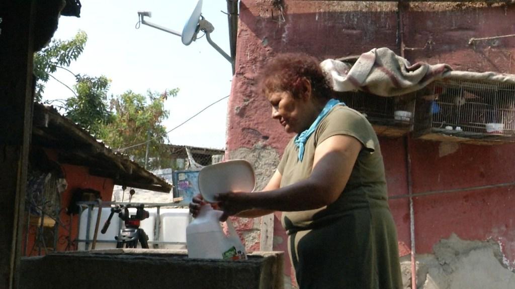María Segovia, residente de Tijuana llena garrafones de agua en los momentos que regresa el agua a su casa para refrescarse en medio de una ola de calor que azota la región.