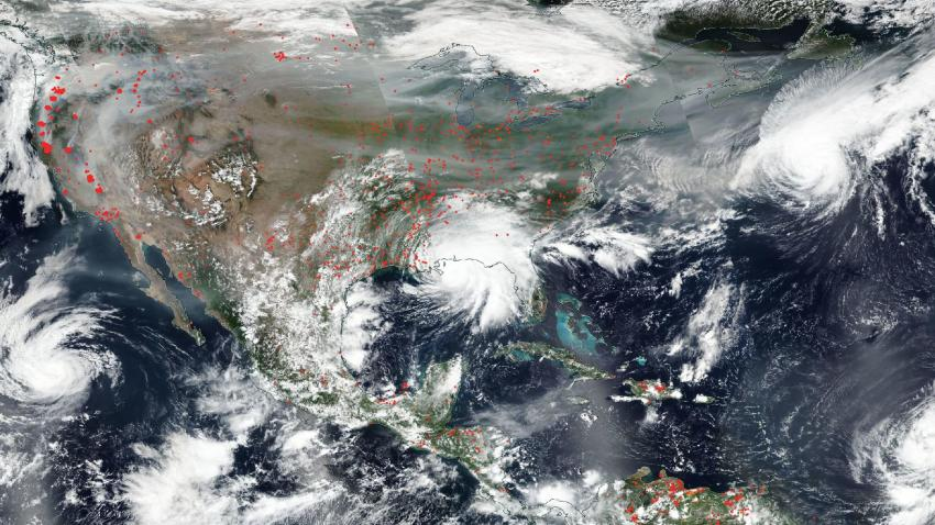A NASA satellite image shows wildfires, heavy smoke and hurricanes.