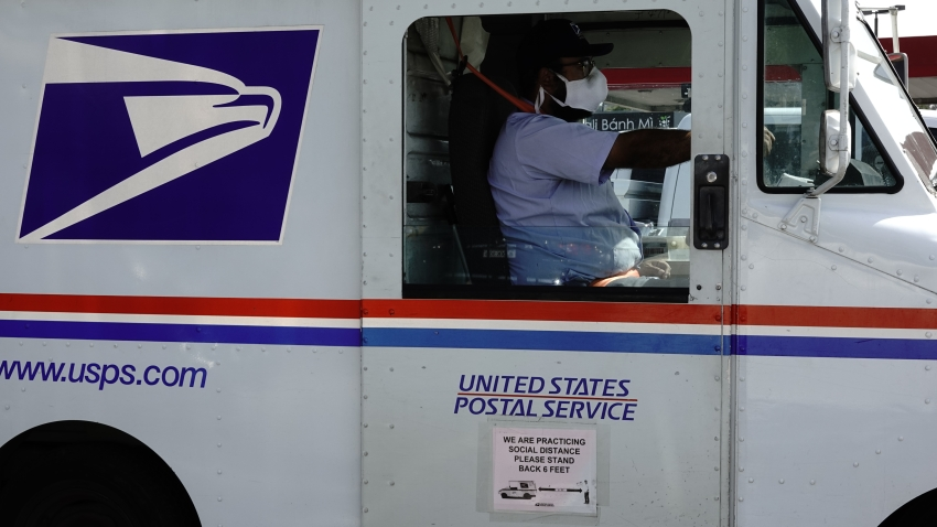 A social distancing sign is displayed on the side of a United States Postal Service (USPS) delivery truck