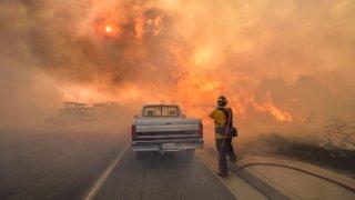 A firefighter battles flames.