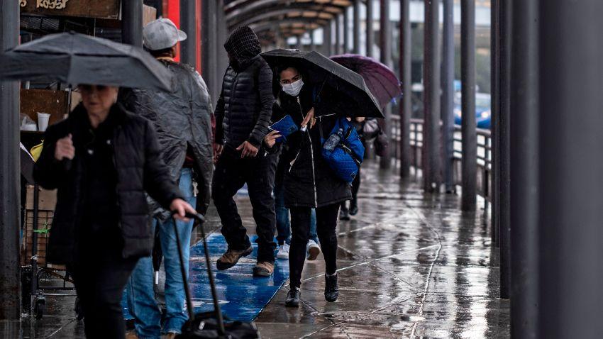 personas cruzando la frontera por San Ysidro con sombrillas en mano