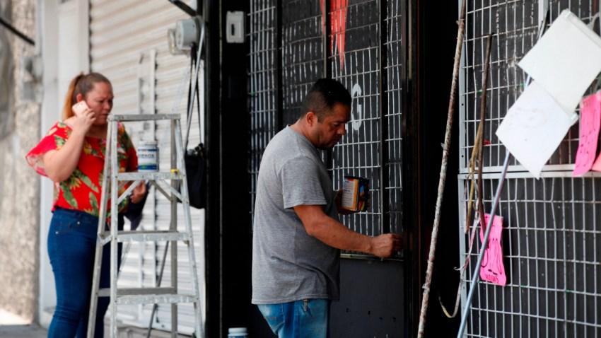 Una mujer habla por teléfono mientras un hombre remoza su negocio