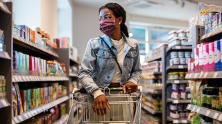 Woman wearing protective face mask buying groceries at a supermarket