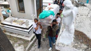 Personas cargan un ataúd en un cementerio mexicano