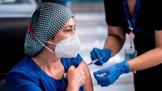 Fotografía cedida por la Presidencia de Chile que muestra a la enfermera Zulema Riquelme mientras recibe la vacuna contra el COVID-19, en el Hospital Metropolitano de Santiago (Chile).