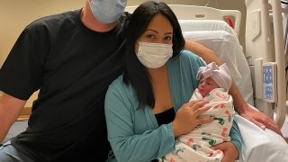 Nick and Melissa Hawke with their newborn, Delmar.