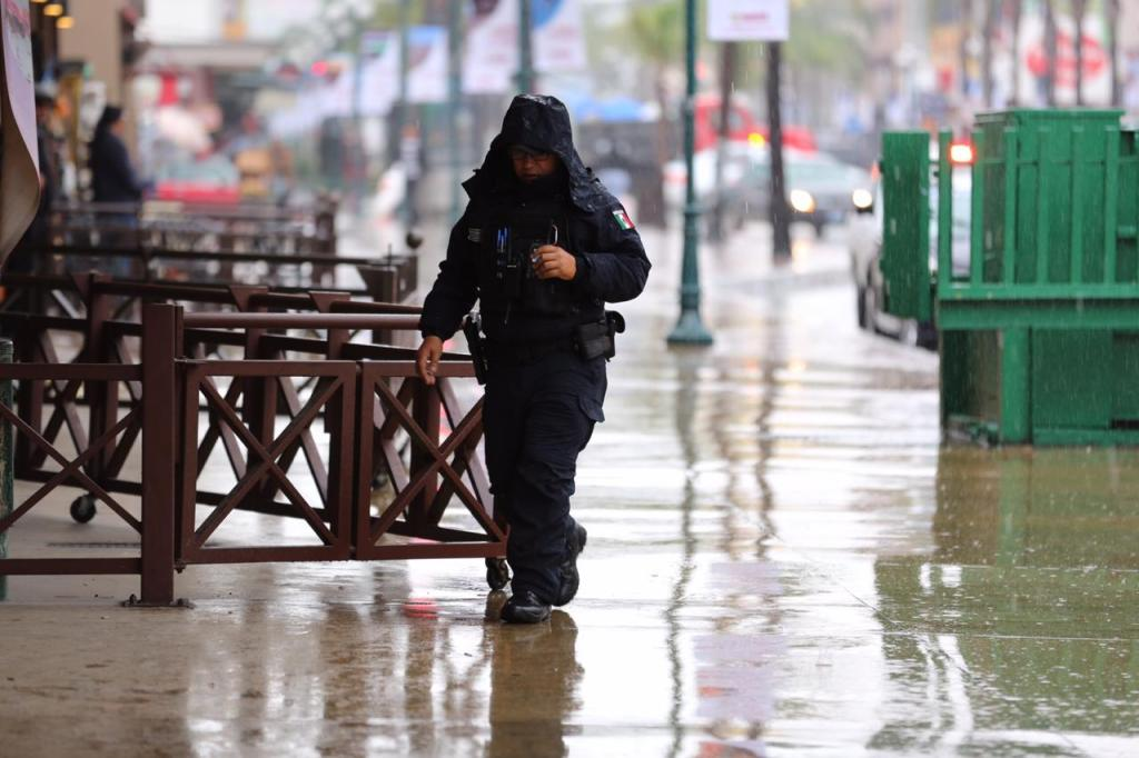 policia municipal de Tijuana caminando bajo la lluvia