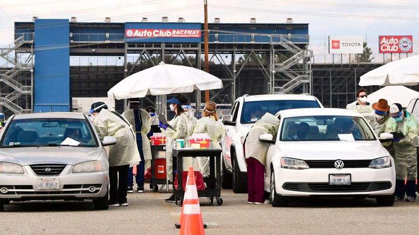 In this Jan. 22, 2021, file photo, healthcare personnel dressed in personal protective gear help inoculate people arriving to receive Covid-19 vaccines at the Fairplex in Pomona, California, one of five mass COVID-19 vaccine sites opened across Los Angeles County this week.