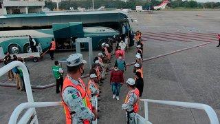 Ciudadanos hondureños suben a un avión para volver a casa, desde México