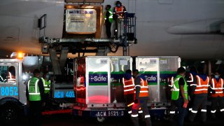 Trabajadores descargan un lote de vacunas AstraZeneca que envío EEUU a México