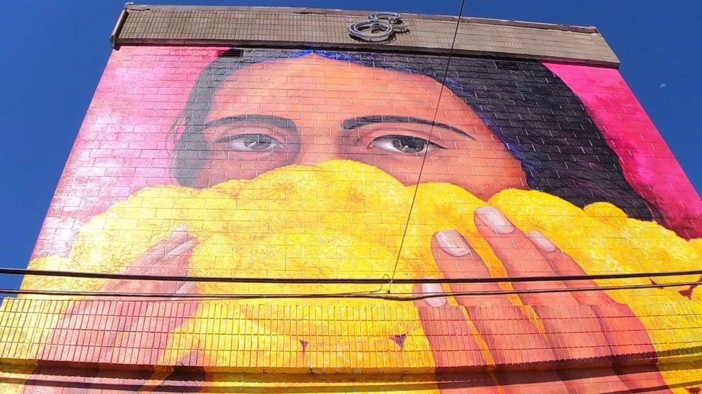 Mural en Barrio Logan de mujer con flores de cempaxúchitl
