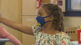 Girl wearing a mask raises her arm in a classroom