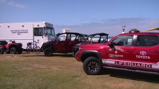 Beach safety vehicles from San Diego police and lifeguards stationed at Mission Beach.