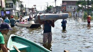 Varios hombres, uno de ellos cargando un colchón, caminan en una inundación en calles de Tabasco