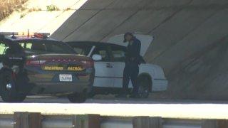 CHP officer inspecting white sedan involved in freeway shooting.