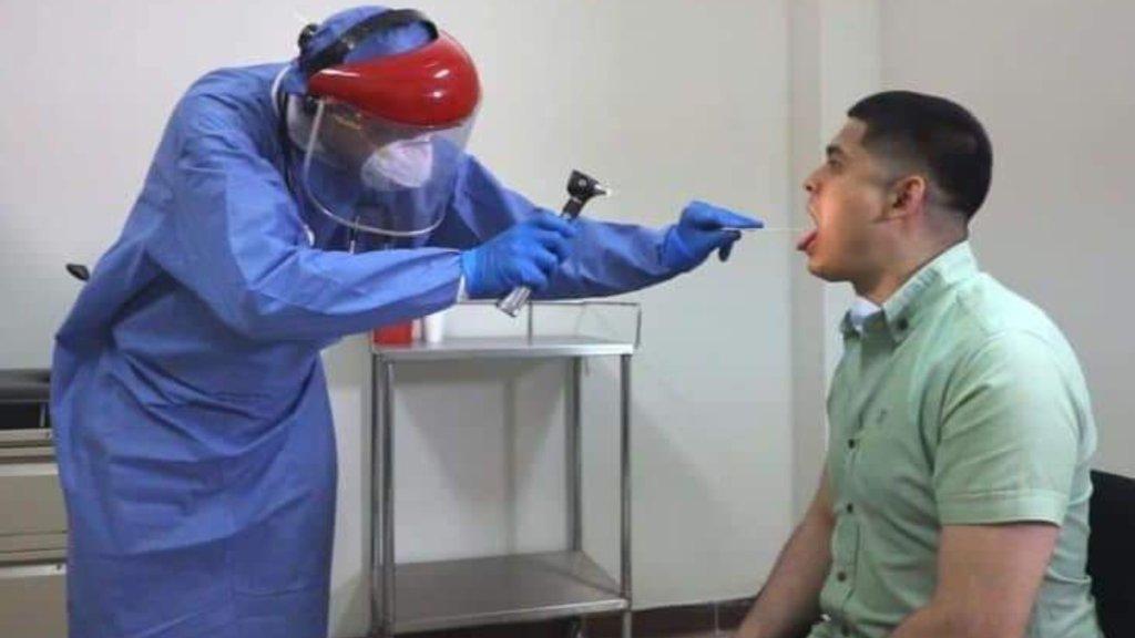 Un médico realiza una prueba a un posible enfermo de COVID-19