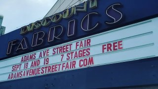 The iconic Discount Fabrics marquee displays the upcoming dates for the 40th Annual Adams Avenue Street Fair.