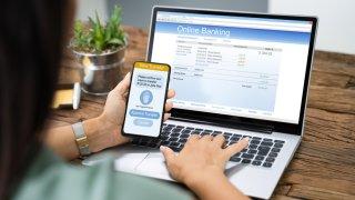 Una persona revisa su cuenta bancaria en una computadora portátil y una transferencia de dinero en su teléfono móvil.