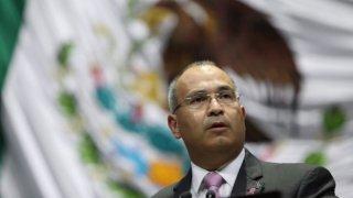 Fotografía de un hombre maduro, de lentes y con traje frente a una bandera de México