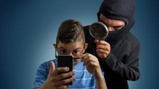 Foto concepto que muestra a joven con celular y alguien enmascarado que espía lo que hace con el dispositivo.
