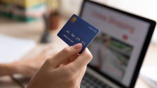 Foto de una persona con una tarjeta de crédito en la mano y una computadora portátil al frente.