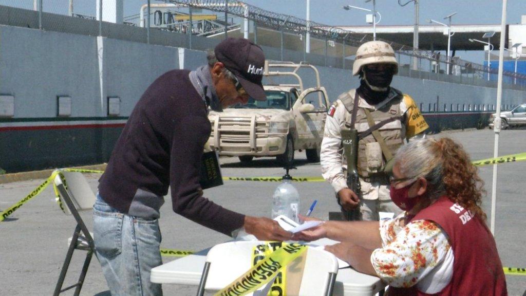 persona llena formulario mientras vigila un militar